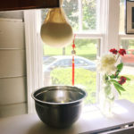 Hanging goat cheese in butter muslin with bowl beneath to catch whey | Little Red Farmstead